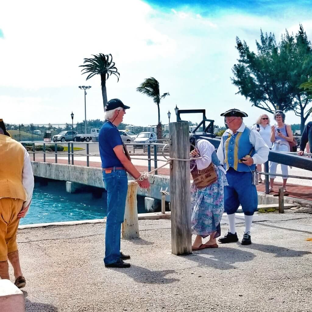 Tourist in St. George's Bermuda is tied to a post as locals do a 17th century reenactment in King's Square.  St. George's Harbor is visible in the background.