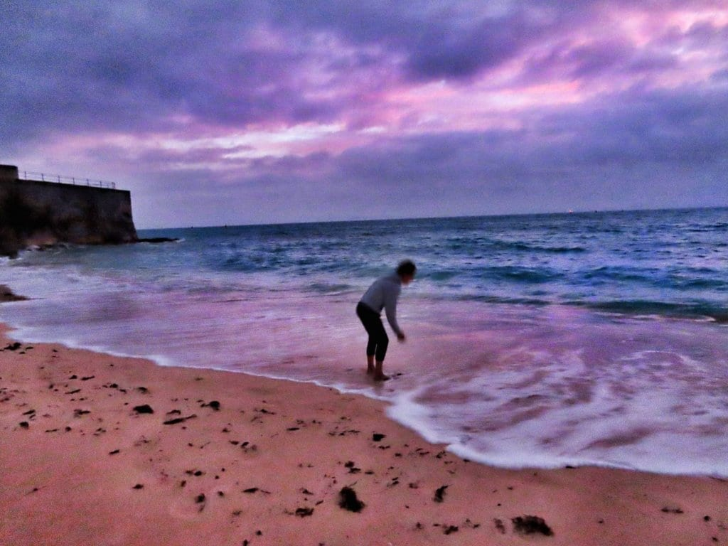 Woman picking up seashells during sunrise at St. Catherine's Beach in St. George's, Bermuda