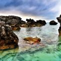 Shallow turquoise waters in Tobacco Bay, Bermuda with stormy skies and jagged rocks coming up out of the ocean.