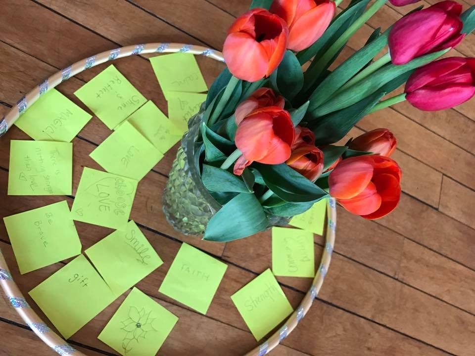 Vase of tulips on the floor with many yellow post-its with notes of positivity during a yoga teacher training.