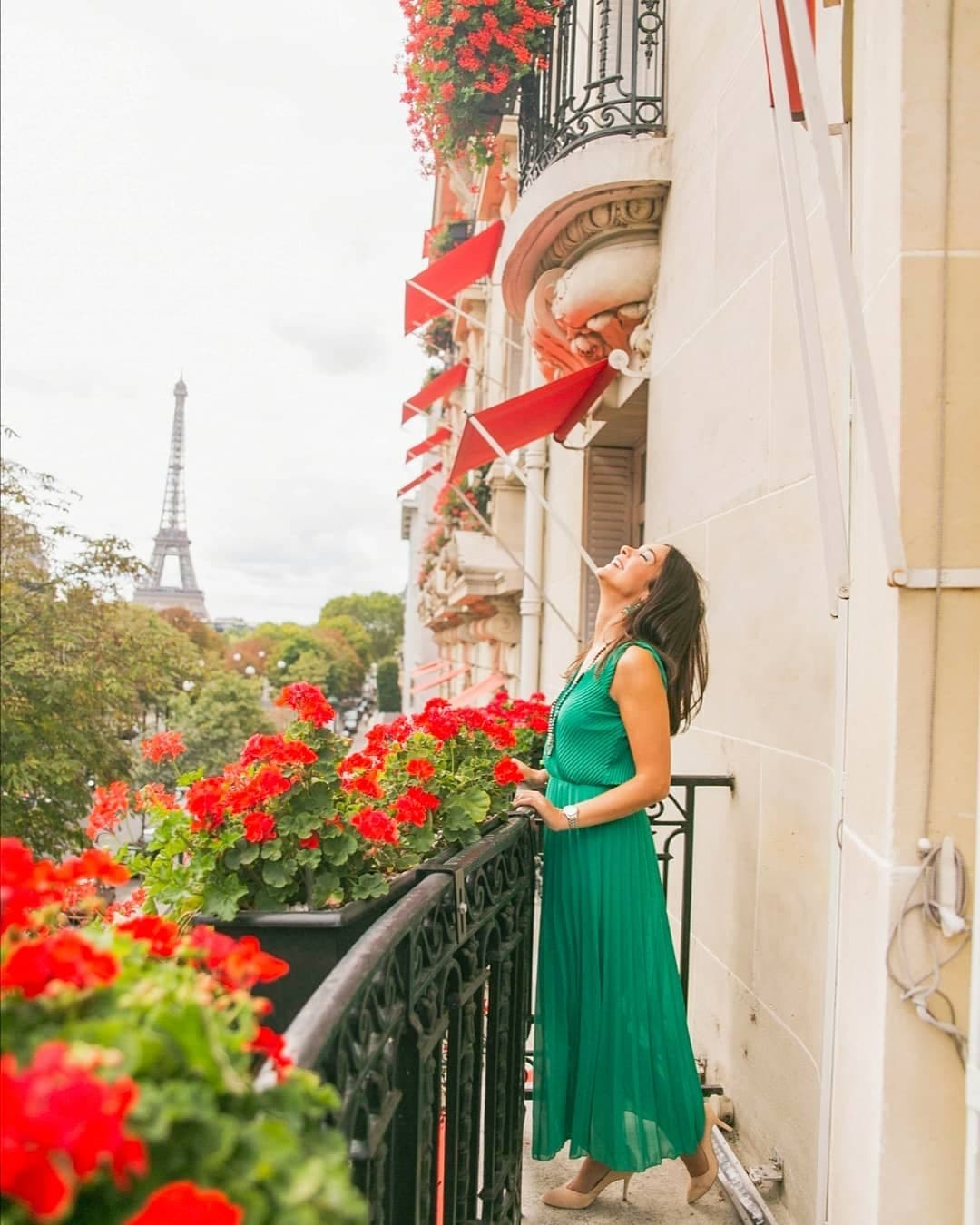 Woman in green dress on red flowered balcony in front of the Eiffel Tower, Paris
