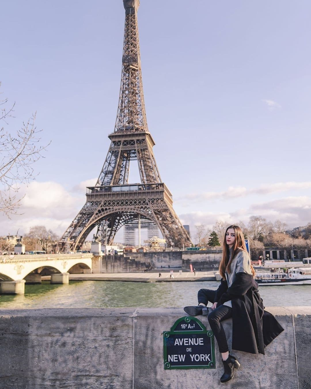 Woman sitting next to Avenue de New York sign in front of the Eiffel Tower