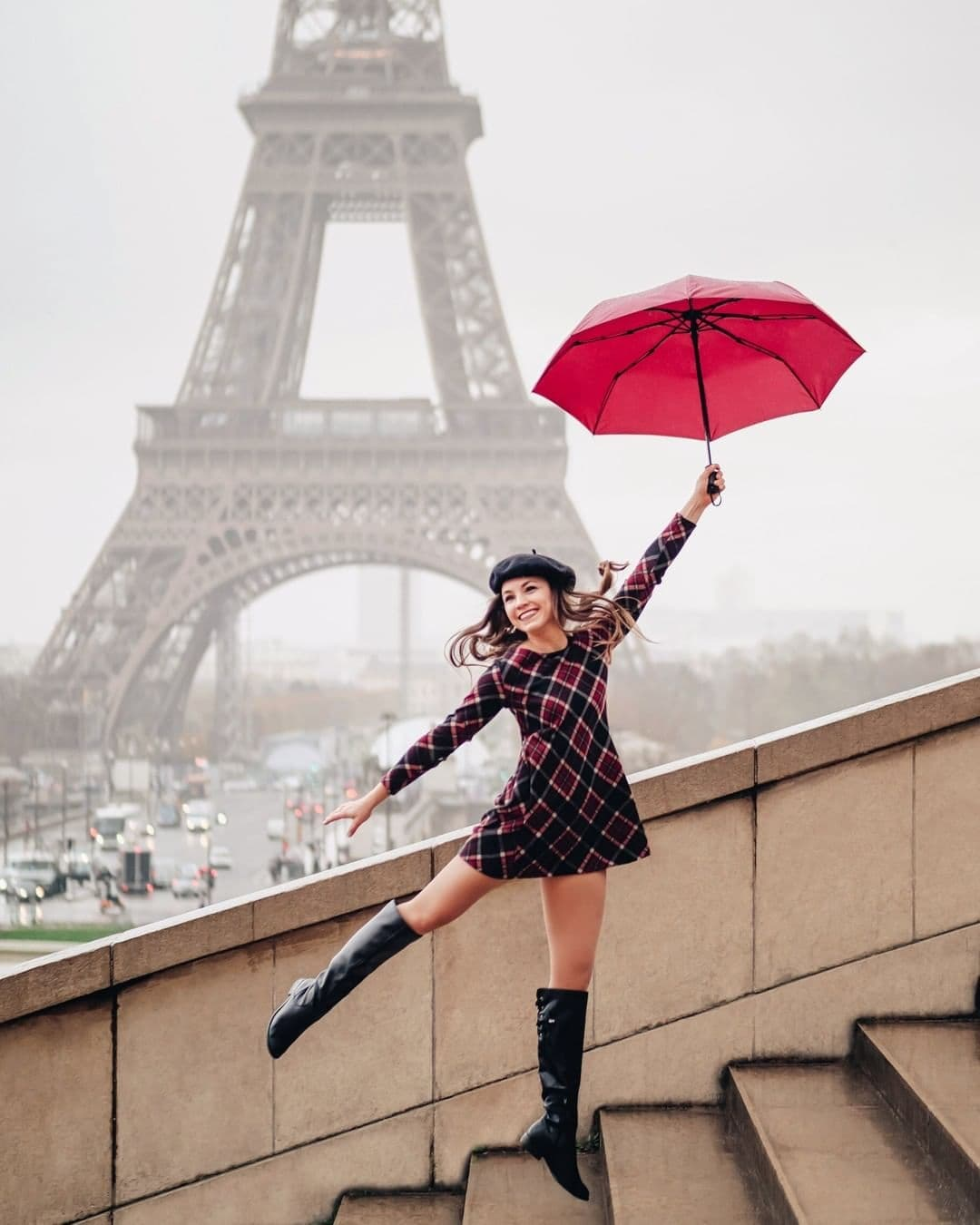 Playful photo of woman on Trocadero steps with umbrella in front of Eiffel Tower