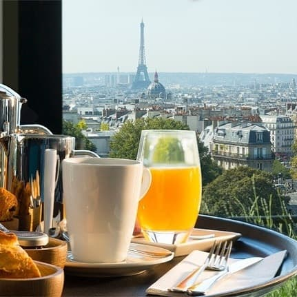 Tall glass of orange juice with coffee and the Eiffel Tower in the background