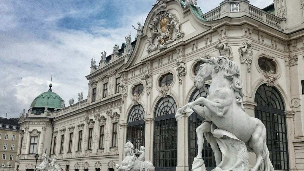 Side angle view of Hofburg Palace with statues of horses bucking and the iconic seafoam green domed roof.