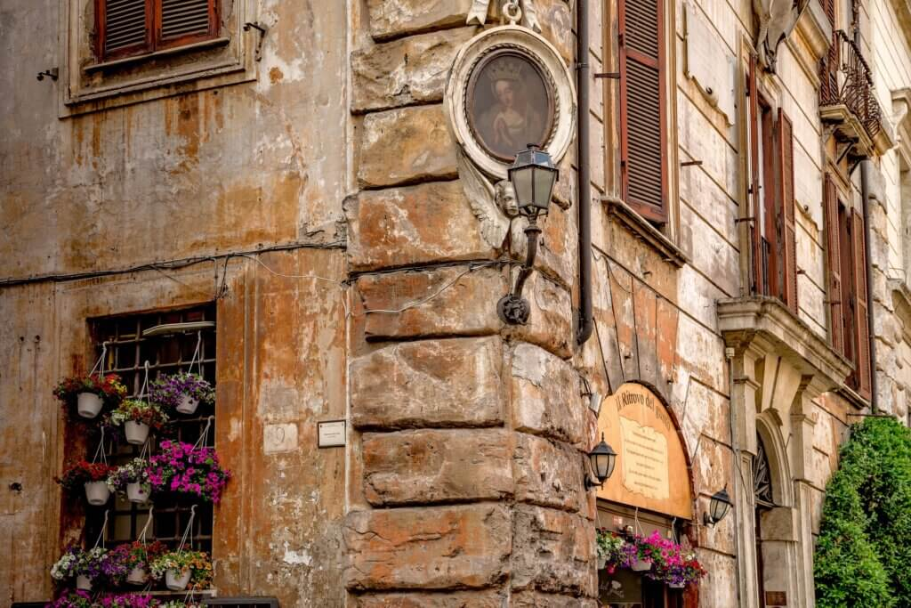 Exterior of an old Roman building in slight degradation with flowers hanging in the windows.