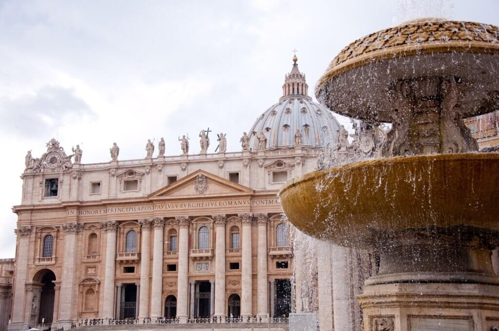 St. Peter's Basilica seen in the background with a spraying fountain in the foreground to the right of the photo.