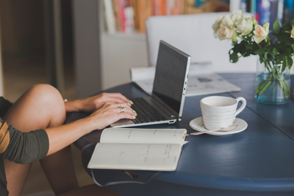 Woman typing on a computer with a nearby coffee cup, working as a digital nomad.
