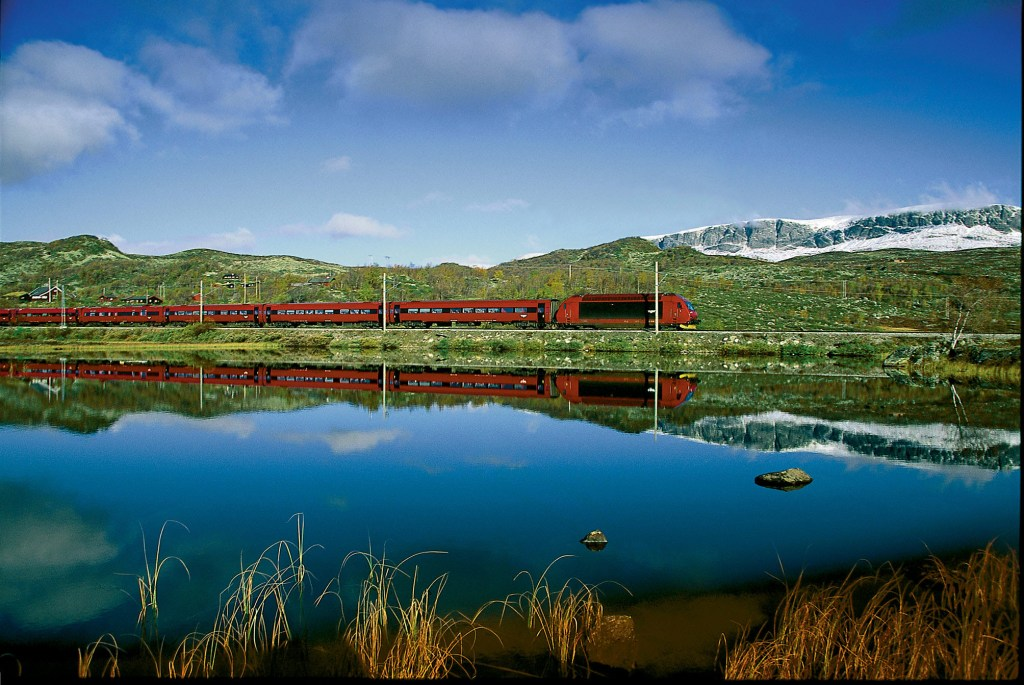 Red train reflected on the lake with snow covered mountains in the background.