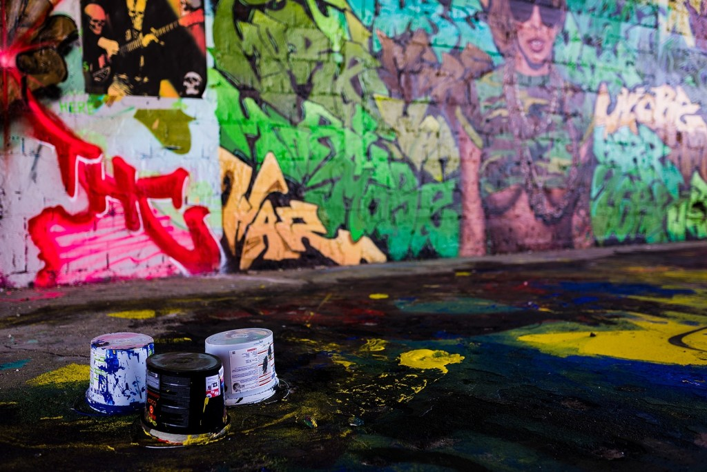 Colorful street art in Berlin with paint cans strewn about on the ground.