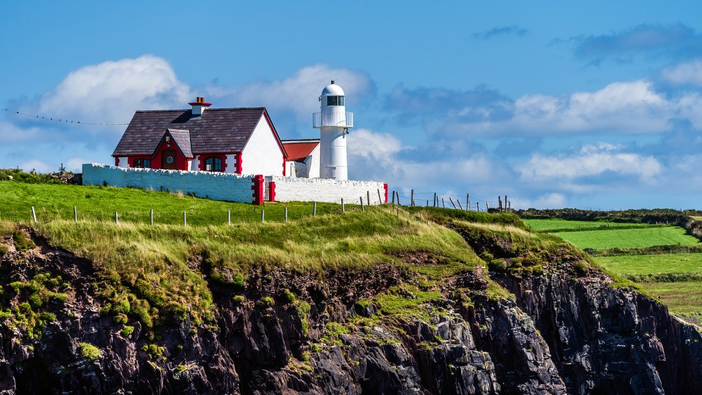 Red and white lighthouse and farm building on Dingle Peninsula in Ireland.