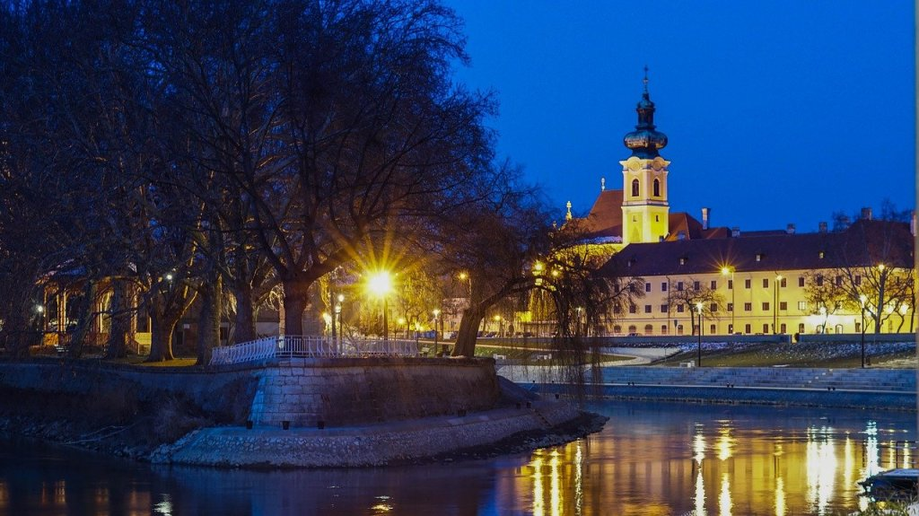 Gyor City Hall illuminated in gold lights at night, one of the best day trips from Budapest.