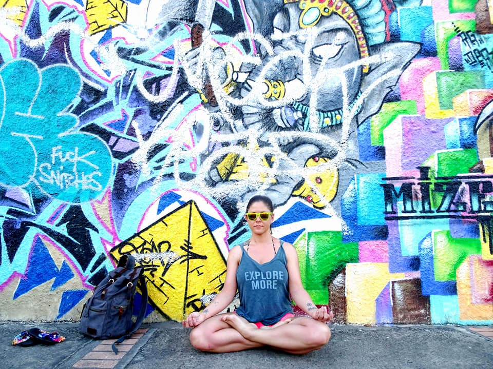 Woman in padmasana lotus pose on the sidewalk next to some street art of Ganesh in Guadeloupe.