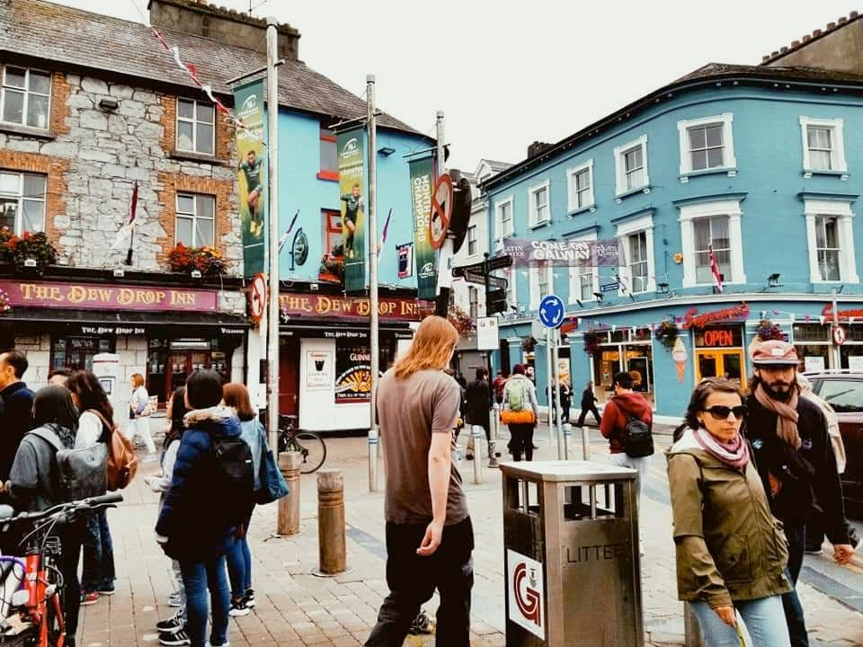 People walking around the busy Latin Quarter in Galway, Ireland with colorful blue buildings in the square.