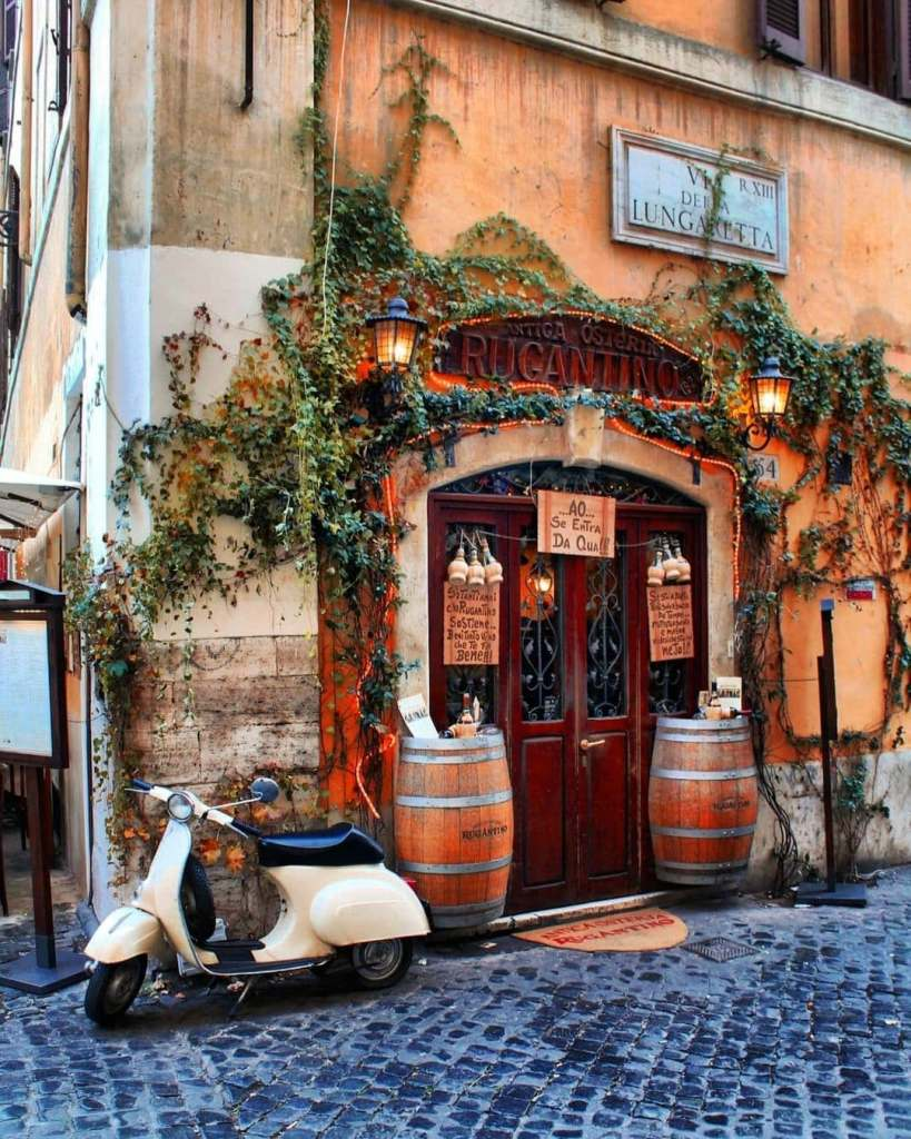 Storefront in Trastevere with a white vespa outside the door, which is flanked by two wine casks.  One of the most Instagrammable places in Rome.