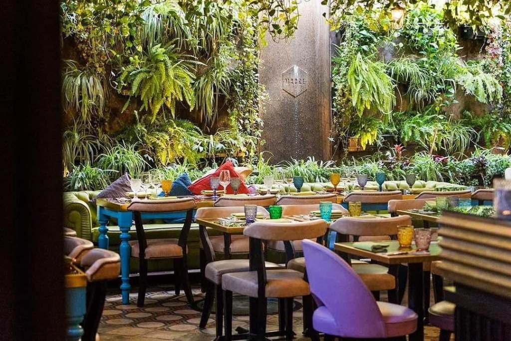 Plant-covered walls and colored glasses adorn the interior of Madre restaurant in Rome, ITaly.