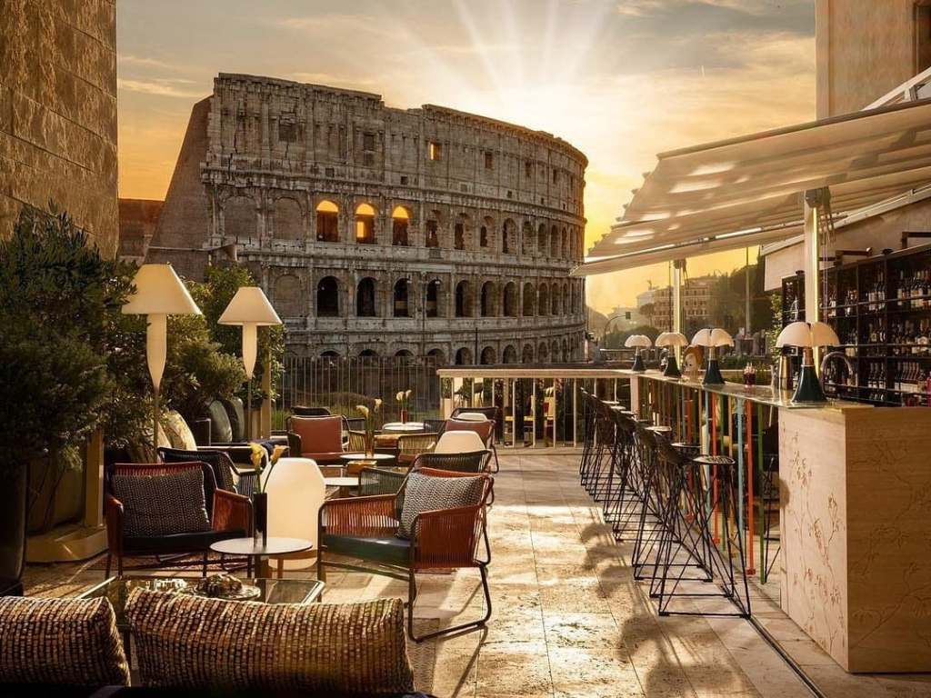 Rooftop MIchelin-starred restaurant Aroma during sunset with the Colosseum in the background, one of the most Instagrammable places in Rome.