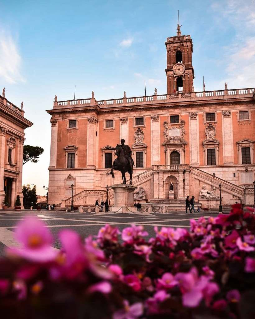 Piazza di Campidoglio, with a large tower and pink-ish hued buildings.  There are magenta flowers in the foreground at the bottom of the image.