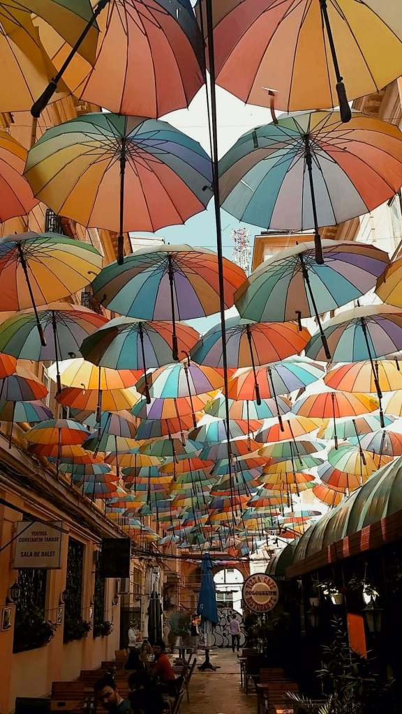Colorful umbrellas hanging above tables at a Romanian cafe.
