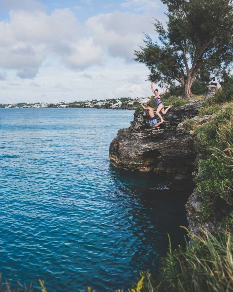 Two people cliff-jumping at Admirality House Park in Bermuda