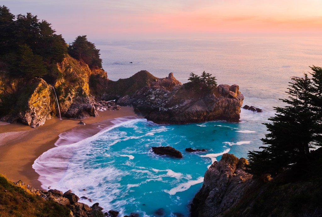 Waves crashing on the shores of Big Sur, California during a pink and orange sunset.