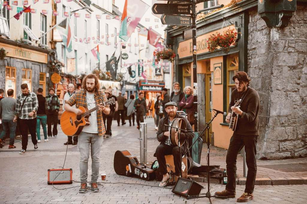Street performers (buskers) in a busy square in Galway, Ireland.