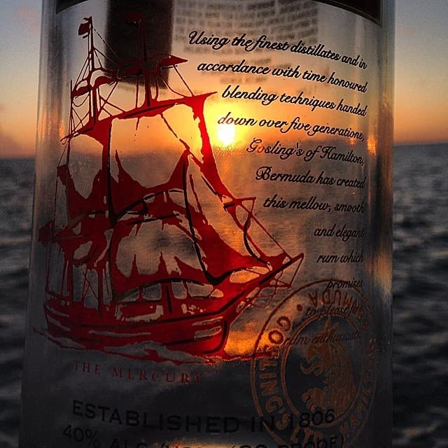 Close-up of an empty bottle of Gosling's rum with the sun set shining behind the transparent bottle, on Bermudian waters