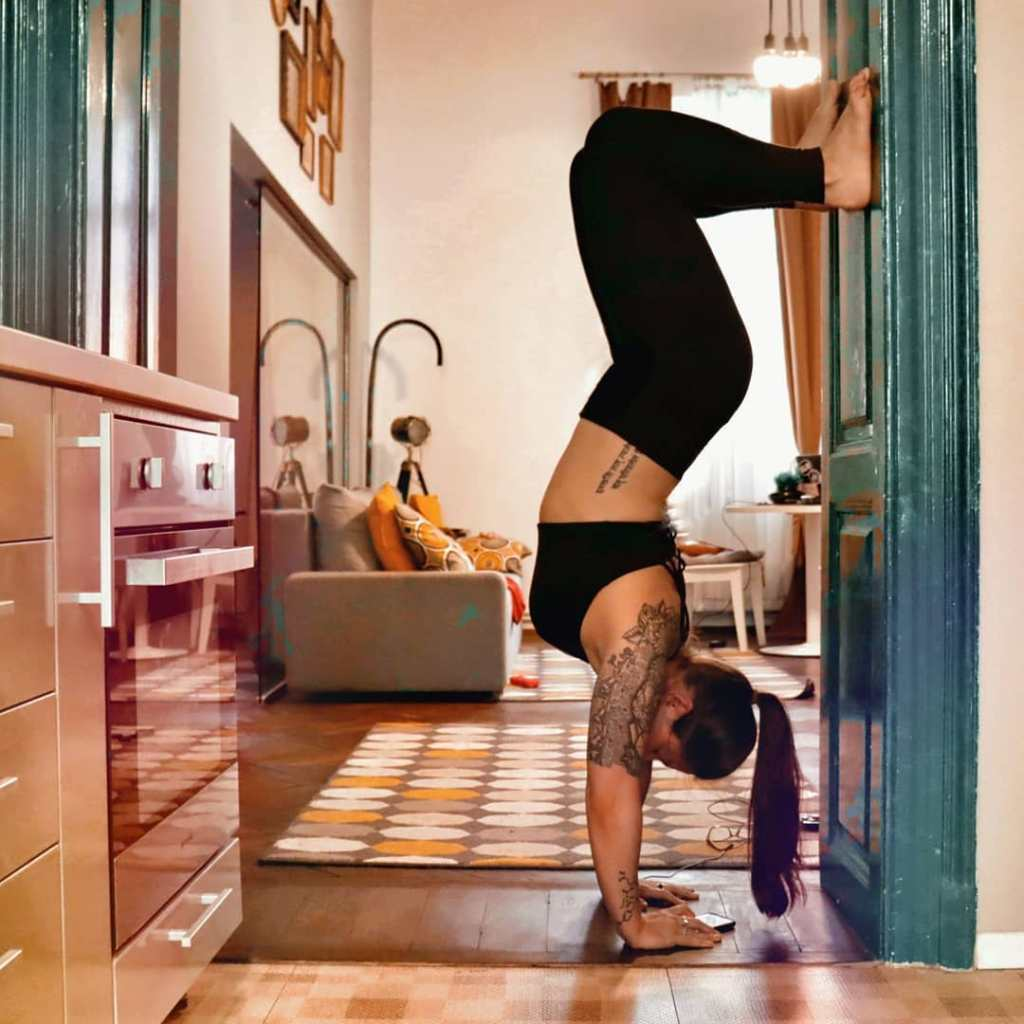 Woman doing a hand stand in an apartment doorway in Cluj-Napoca, Romania.