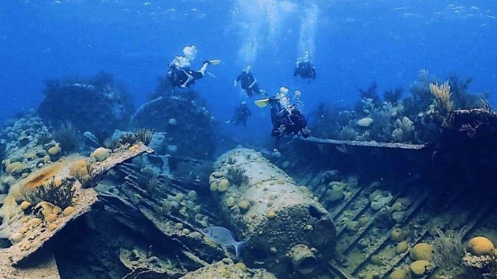 People scuba diving exploring a ship wreck in Bermuda