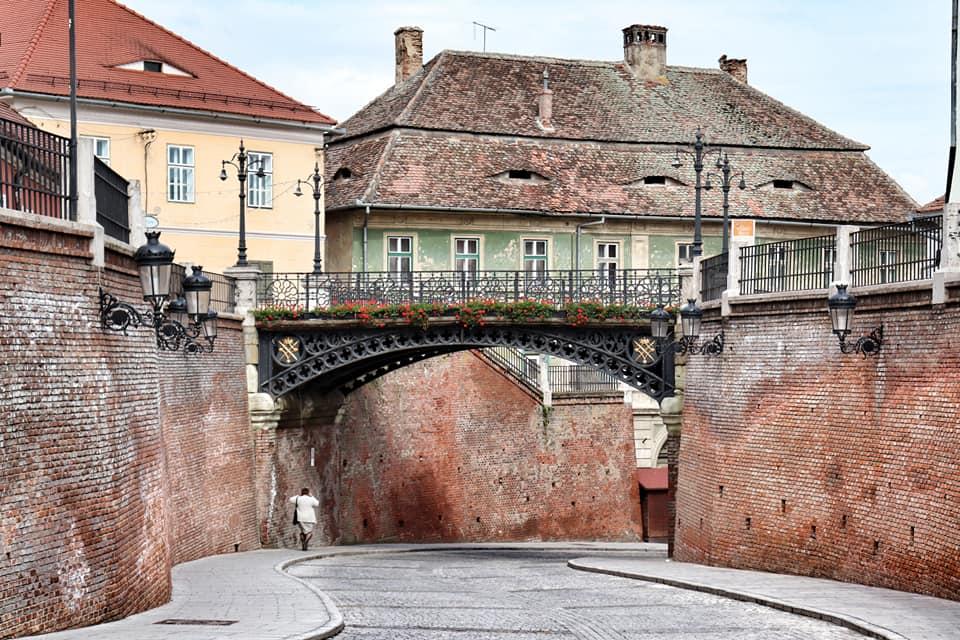 Woman walking under the Bridge of Lies in the Old Town of Sibiu, Romania.