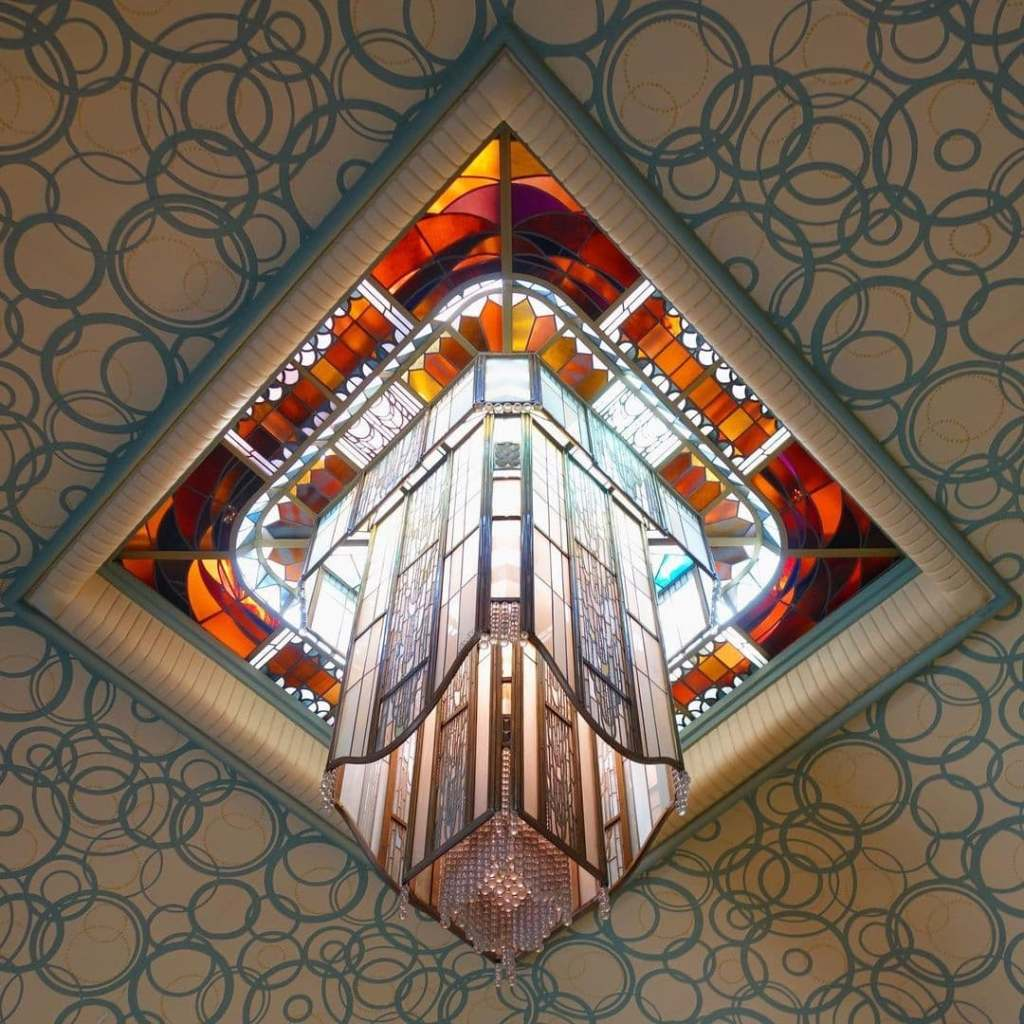 Crystal and glass art deco light with hues of oranges and browns hanging from the Carnegie Library ceiling in Reims, France.