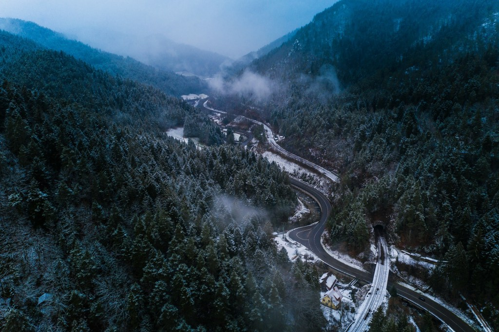 Drone view of winding, remote streets in the evergreen Black Forest of Germany with snow scattered throughout.