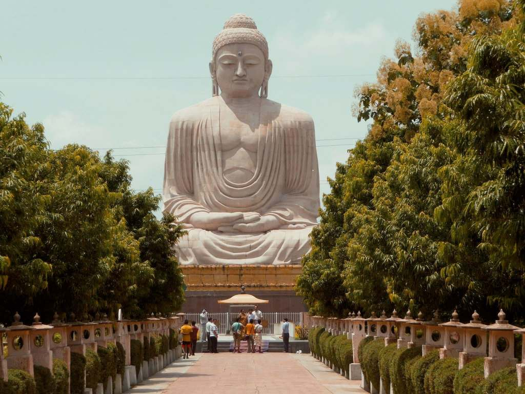 Large Buddhist statue in Bodhgaya, India with trees on either side.