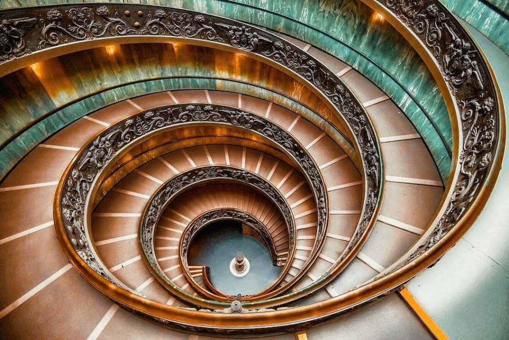 Bramante staircase at the Vatican in hues of orange and aqua.