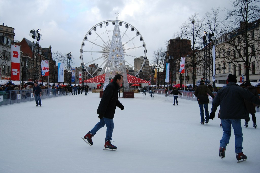 People ice skating in the foreground at a Christmas market in Brussels, Belgium.  In the background, you can see the large Ferris wheel and Christmas decorations.