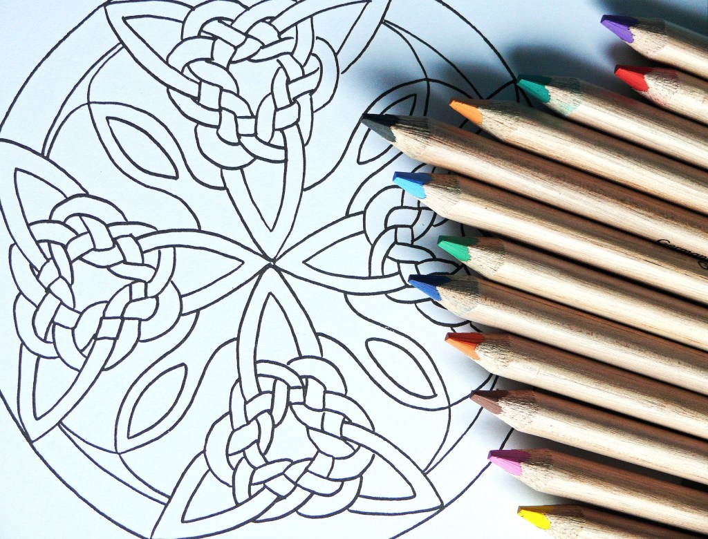 Blank mandala coloring page with colored pencils, a great idea for digital nomad job to sell on Etsy.