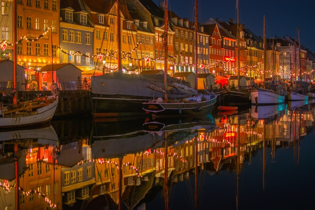 Nyven Christmas market in Copenhagen, Denmark.  Photo is taken from the water and shows a row of boats lining the pier, Christmas lights, and decorated Christmas stalls selling handicrafts and food.