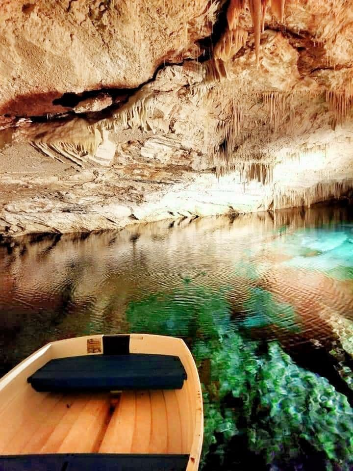 Small wooden boat in the turquoise water of the crystal caves in Bermuda.