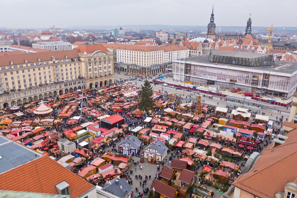 Aerial view of the crowded Christmas market in Dresden, Germany.  Visible are many little stalls with red roofs, Christmas trees, and crowds of people enjoying the market.