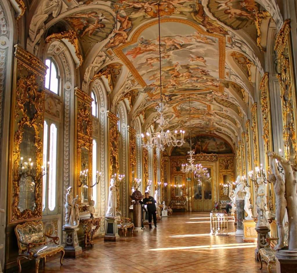 Elaborate hall with gold details, painted frescoes on the ceiling, sculptures, and glass chandeliers at Galleria Doria Pamphilj, one of the most beautiful places in Rome.