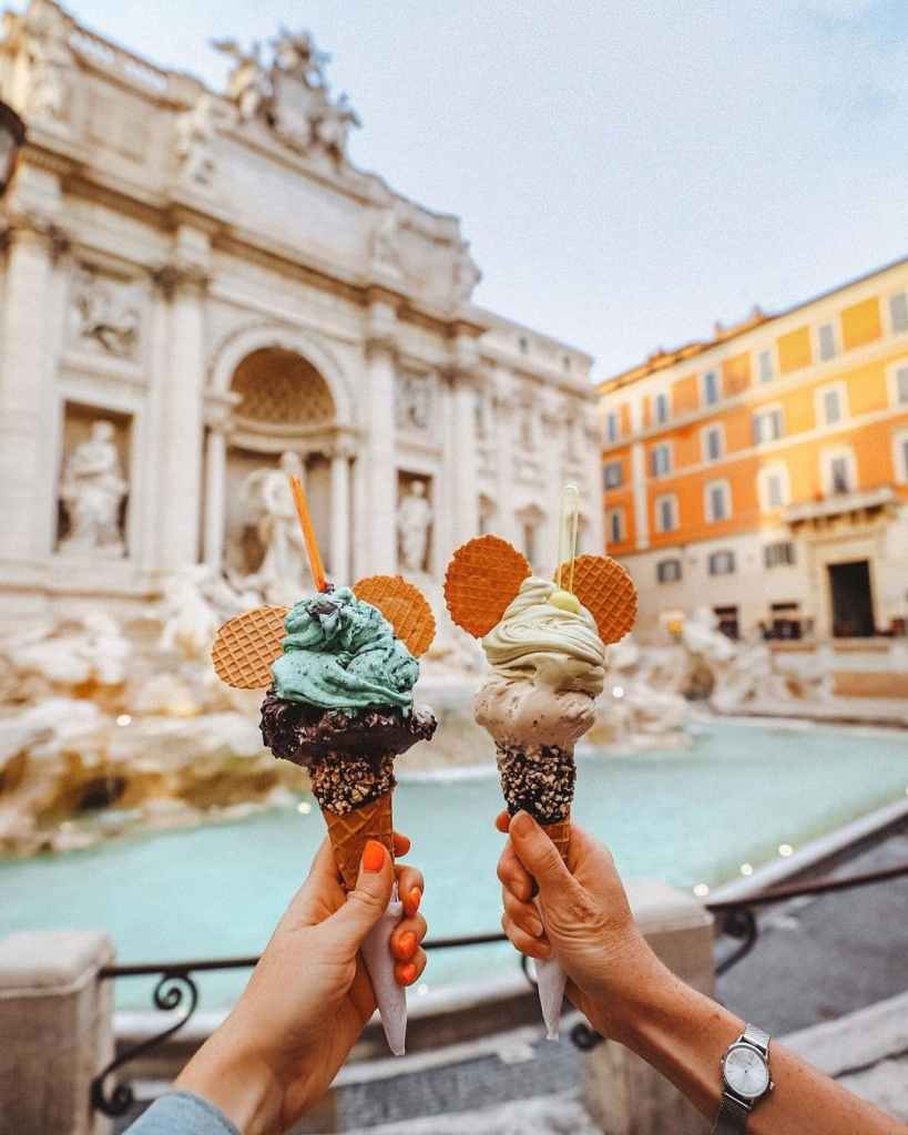 Two outstretched women's hands holding gelato cones in front of the Trevi fountain in Rome, Italy.