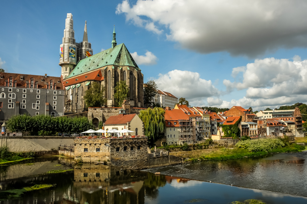 Magical places to visit in Germany - Goertlitz in Germany with rust red and seafoam green roofs, stone buildings lining the river.