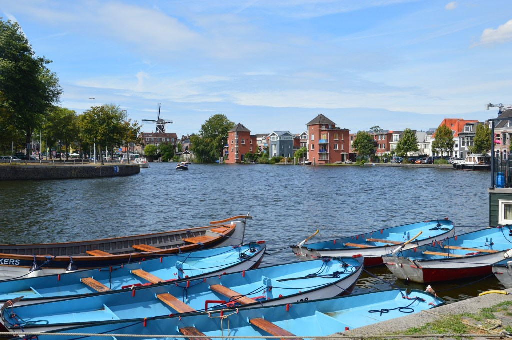 View across the water in Haarlem, Netherlands.  In the foreground there are a number of blue boats, and in the background across the water is a large windmill in one of the best cities to visit in the Netherlands.