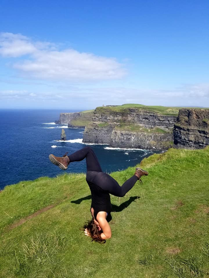 Woman doing headstand at Cliffs of Moher on day trip from Galway