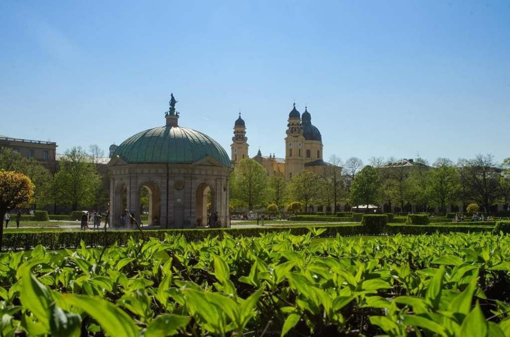Blue dome with buildings in the background and green grass in the foreground, Hofburg, Munich, Germany.