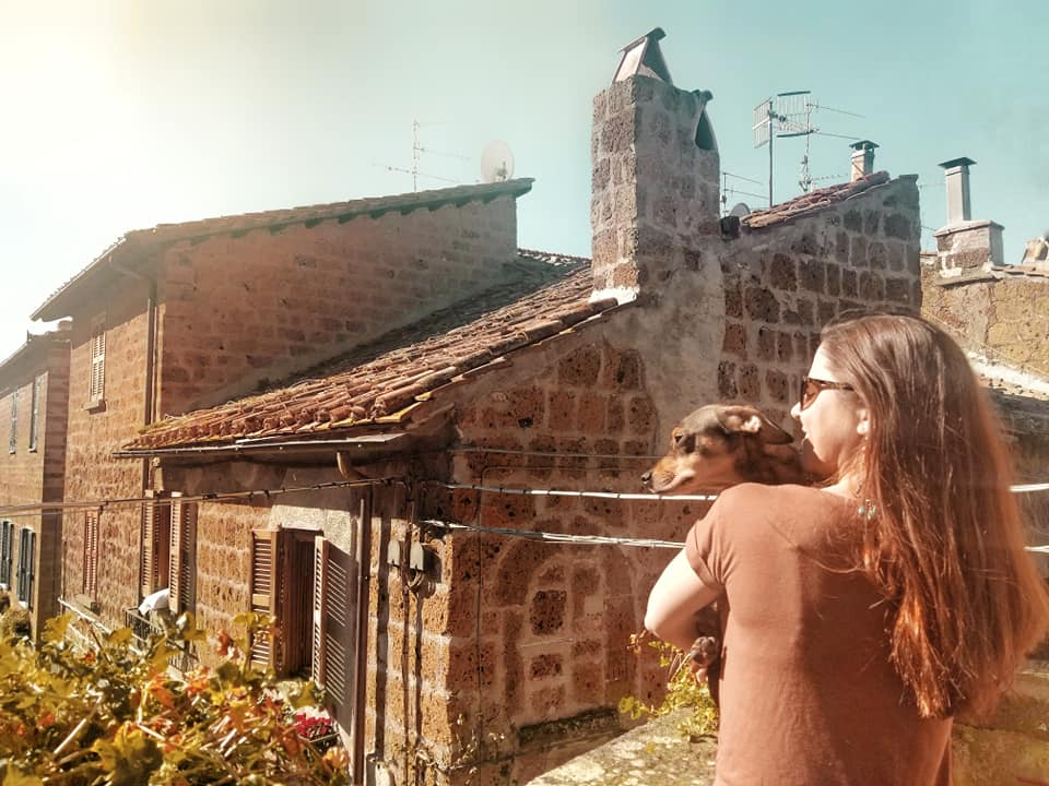 woman holding small dog, overlooking a medieval village in Italy from a loggia