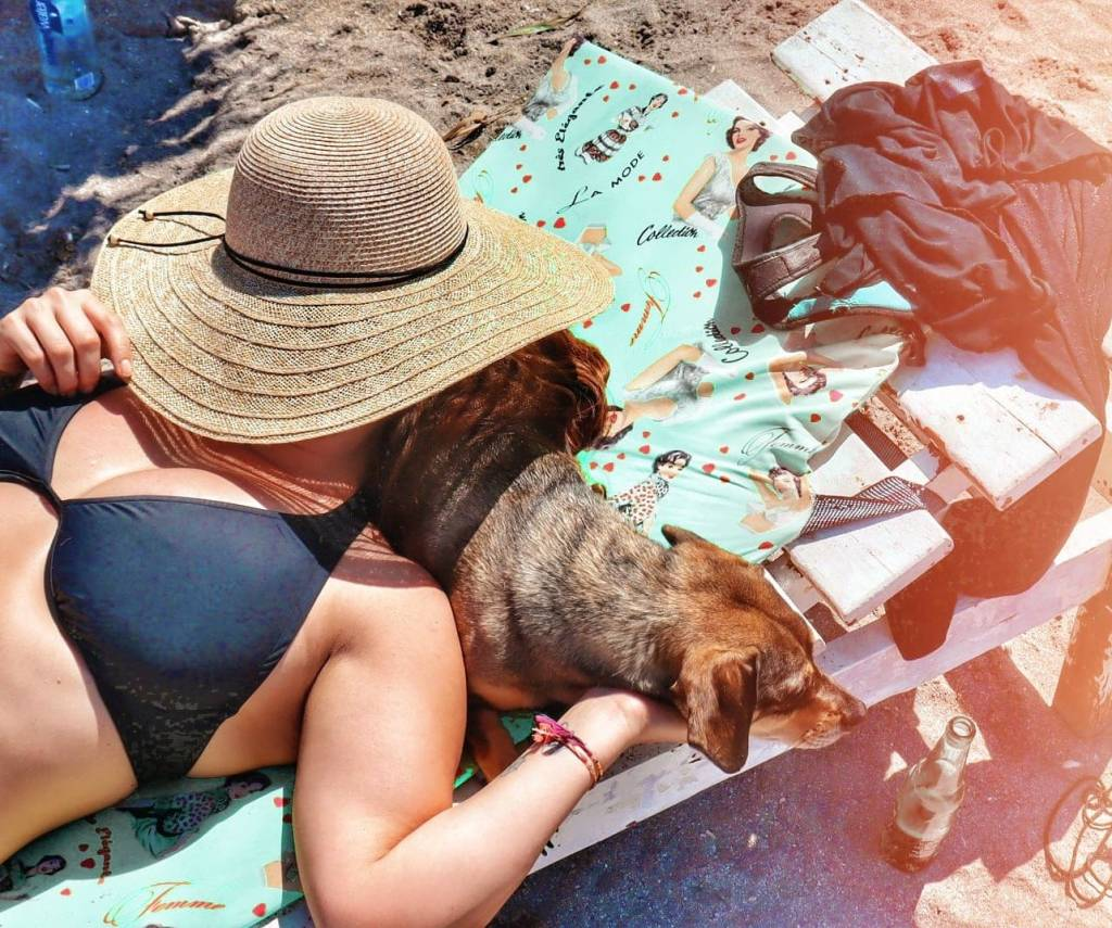 Woman using dog as pillow on beach chair in Vama Veche.