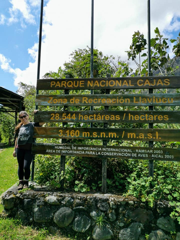 Woman posing and smiling next to a sign for Cajas National Park in Ecuador