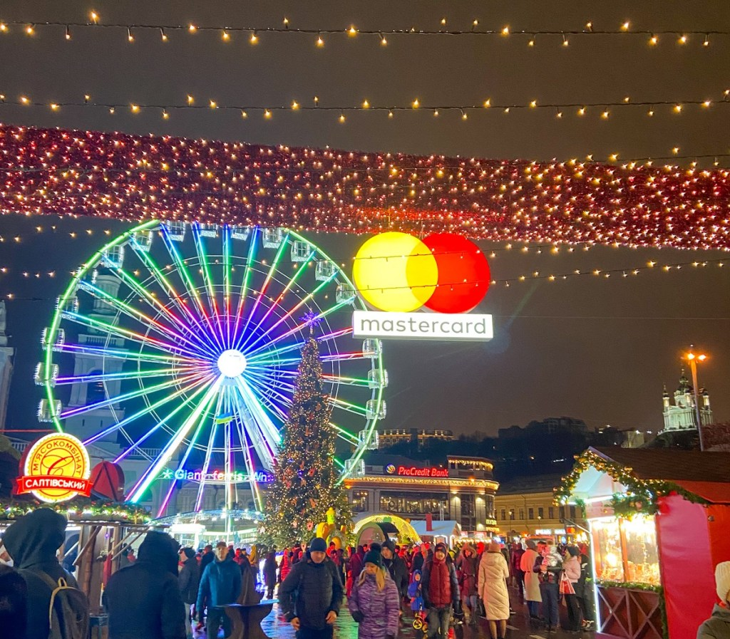 Large, lit ferris wheel and many Christmas lights decorate Kyiv during the city's yearly Christmas markets.