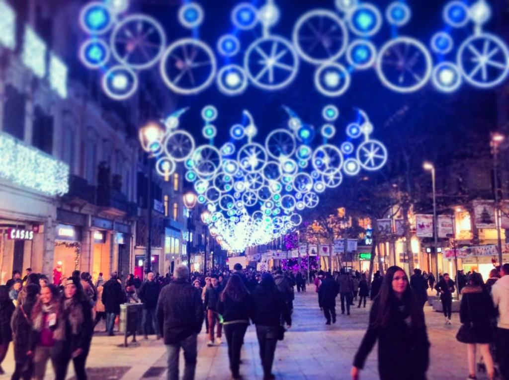 Many blue circular lights are strung above the street in Valletta, Malta during a Christmas market.